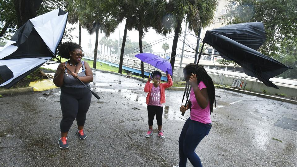 Umbrellas held by Janesse Brown, left, and her daughter Briana Johnson, 12, right, get torn apart by strong winds as Kyra Johnson, 8 watch, while they tried to visit Southbank Riverwalk in Jacksonville, Fla., September 10, 2017, as Hurricane Irma passes the area.