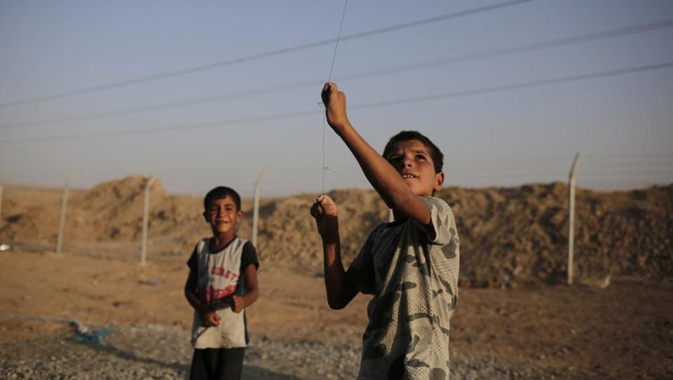 Seven year-old Omar from Mosul flies a kite in the Chamakor camp for displaced. Iraq's Sunni Arabs generally estimated at 15 to 20% of Iraq's 37 million people find themselves at a crossroad after 3 years of war to free them from ISIS rule. Vast numbers displaced from their communities are unsure what their place will be in Iraq's future with the Shiites and the Kurds aiming to alter the demographics of some Sunni areas to impose their own control. (Bram Janssen / AP)