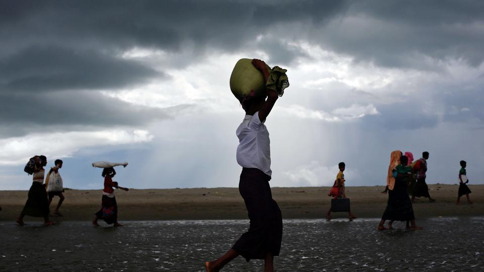 Rohingya refugees walk on the shore after crossing the Bangladesh-Myanmar border by boat through the Bay of Bengal in Shah Porir Dwip, Bangladesh.