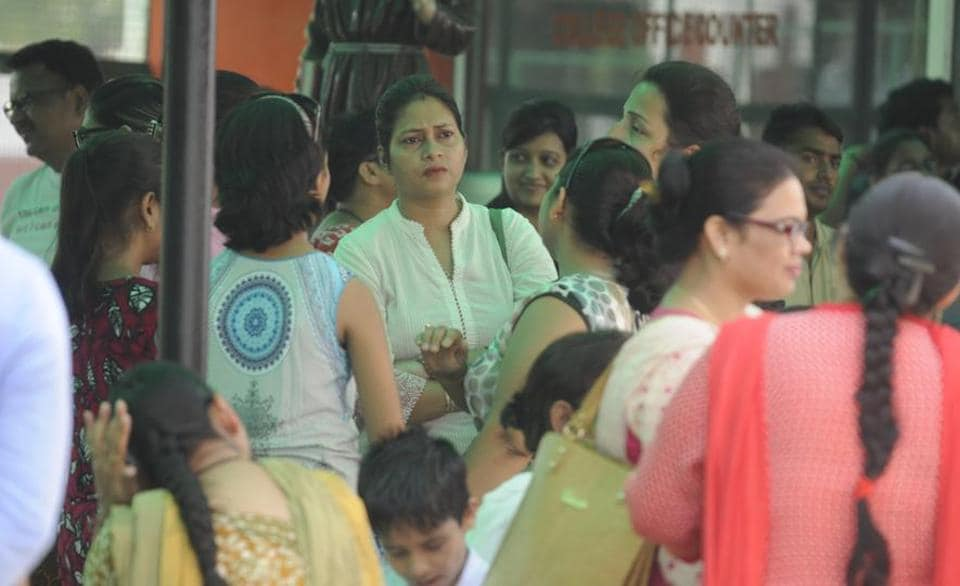 Parents wait outside a school in Lucknow at dispersal time.