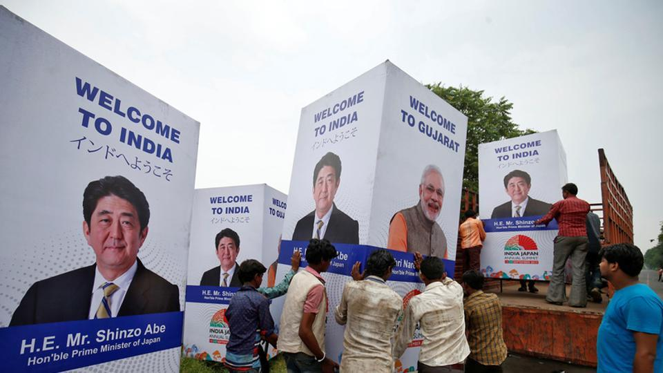 Workers carry a hoarding featuring India's Prime Minister Narendra Modi and his Japanese counterpart Shinzo Abe to load it onto a truck ahead of Abe's visit, in Ahmedabad.