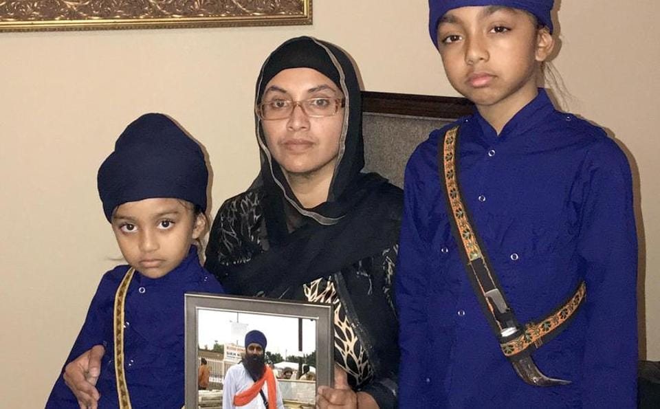 Manjit Kaur, wife of US based Harkewal Singh who went missing during Hemkund Sahib pilgrimage, showing portrait of his husband, along with her kids.