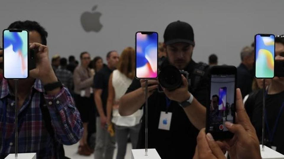Attendees take pictures of new iPhone models during an Apple launch event in Cupertino, California, on Tuesday.