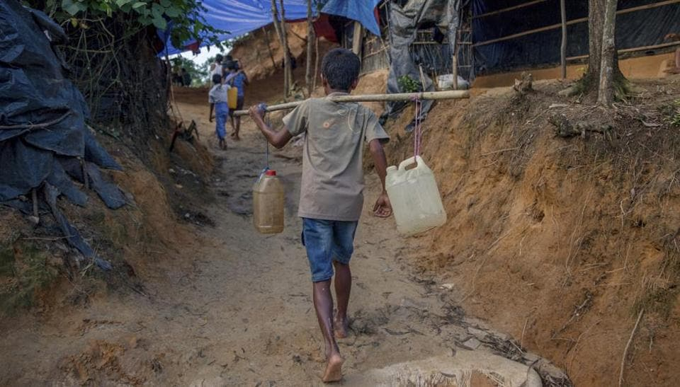 A Rohingya Muslim boy, who crossed over from Myanmar into Bangladesh, carries jerry cans filled with water collected from a nearby hand pump at Balukhali refugee camp, Bangladesh, on Wednesday.