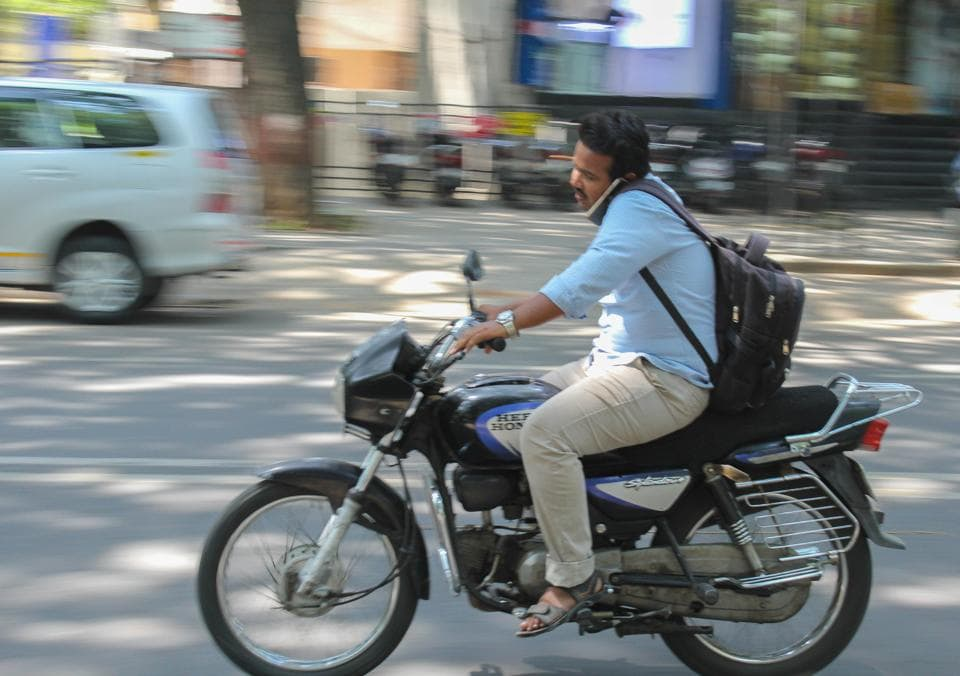 Man riding motorcycle without helmet on JM road in Pune.