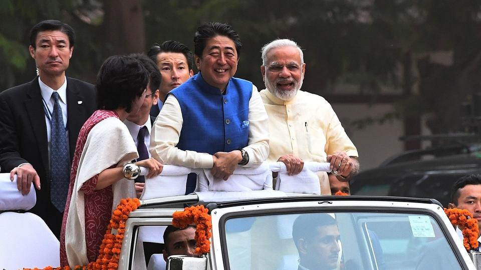 Japanese Prime Minister Shinzo Abe (C) and his wife Akie Abe (L) ride atop a vehicle with Narendra Modi (R) as they arrive to visit Sabarmati Ashramand in Ahmedabad on September 13, 2017.