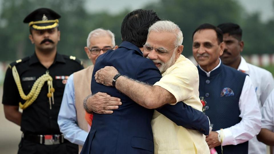 This handout photograph released by the Press Information Bureau (PIB) shows Prime Minister Narendra Modi (R) hugs Japanese Prime Minister Shinzo Abe at Ahmedabad airport.