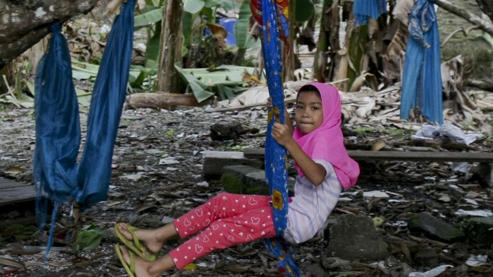 A Rohingya Muslim girl sits on a makeshift swing outside her house in Klang, outside Kuala Lumpur, Malaysia, on Tuesday.