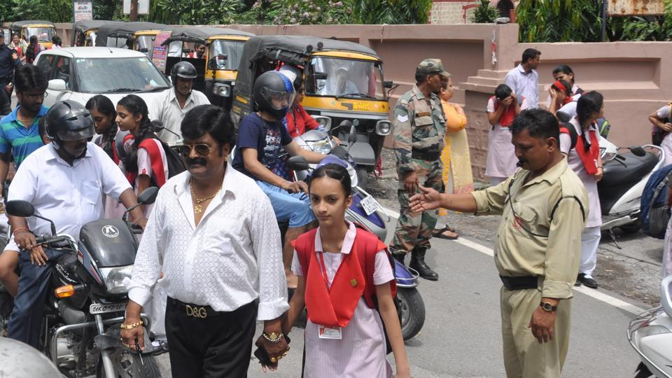 Parents and students come out of a school in Dehradun.