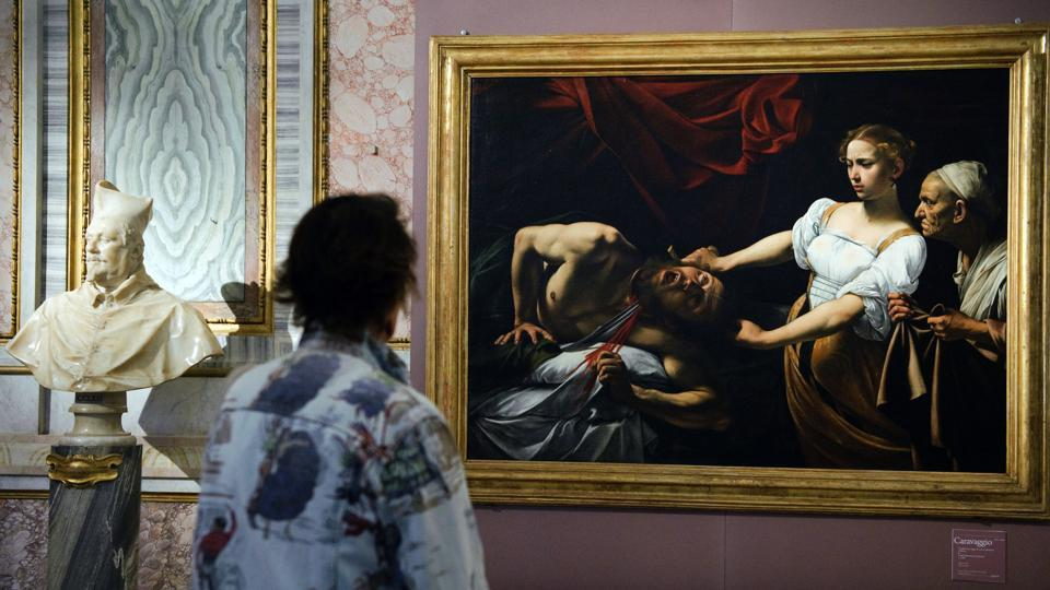 A journalist stands in front of Caravaggio's painting Judith Beheading Holofernes during the opening of the exhibition Caravaggio and Bacon at the Borghese museum in Rome on September 30, 2009.