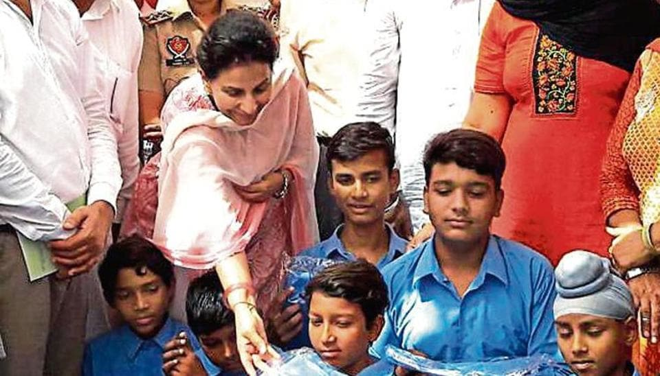 Former Union minister Preneet Kaur distributing uniforms and books among students at Ablowal school in Patiala.