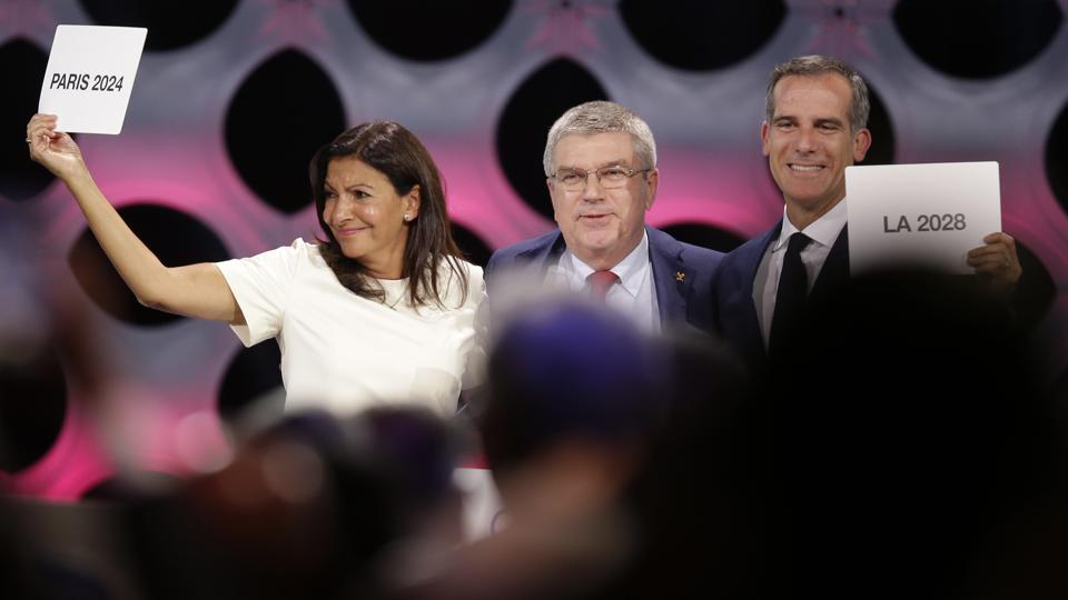 International Olympic Committee (IOC) President Thomas Bach (C) stands between Paris Mayor Anne Hidalgo, (L) and Los Angeles Mayor Eric Garrett (R) at the end of the IOC session in Lima, Peru, Wednesday, Sept. 13, 2017.  (AP)