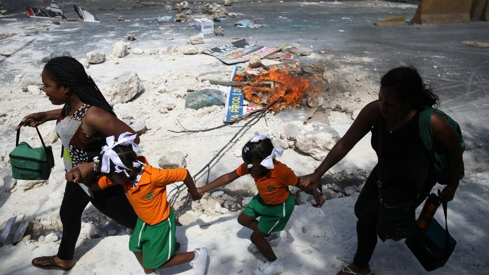 Two women and two girls walk past a barricade during a demonstration against the government in Port-au-Prince, Haiti. Meanwhile, if providing an income tax certificate is needed for administrative tasks such as renewing a license, a 10,000-gourde payment will only be required from those earning more than 60,000 gourdes a year. Officials hope the move will encourage more Haitians to declare their income. (Andres Martinez Casares / REUTERS)