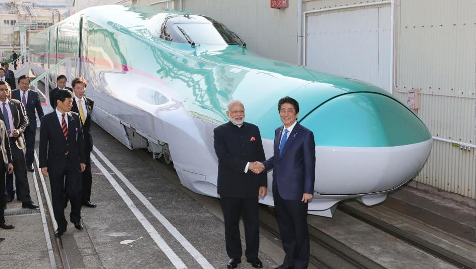 Prime Minister Narendra Modi and his Japanese counterpart Shinzo Abe shaking hands in front of a Shinkansen train during their inspection of a bullet train manufacturing plant in Kobe, Hyogo prefecture.