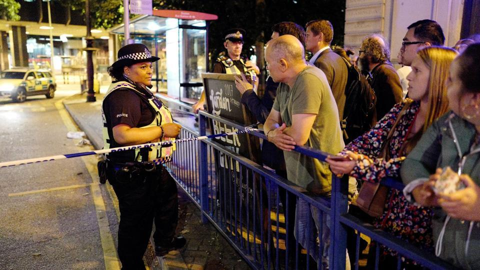 Police and commuters are seen outside Euston Station after police evacuated the area following a security alert in London, Britain, August 29.