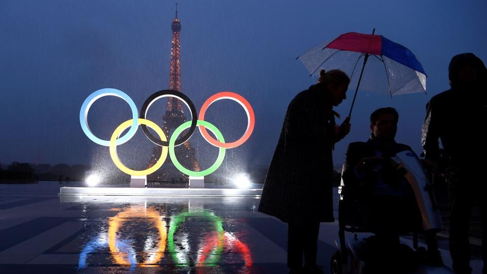 People gather in the rain beside the Olympics Rings on the Trocadero Esplanade near the Eiffel Tower in Paris, on September 13, 2017, after the International Olympic Committee named Paris host city of the 2024 Summer Olympic Games.  (AFP)