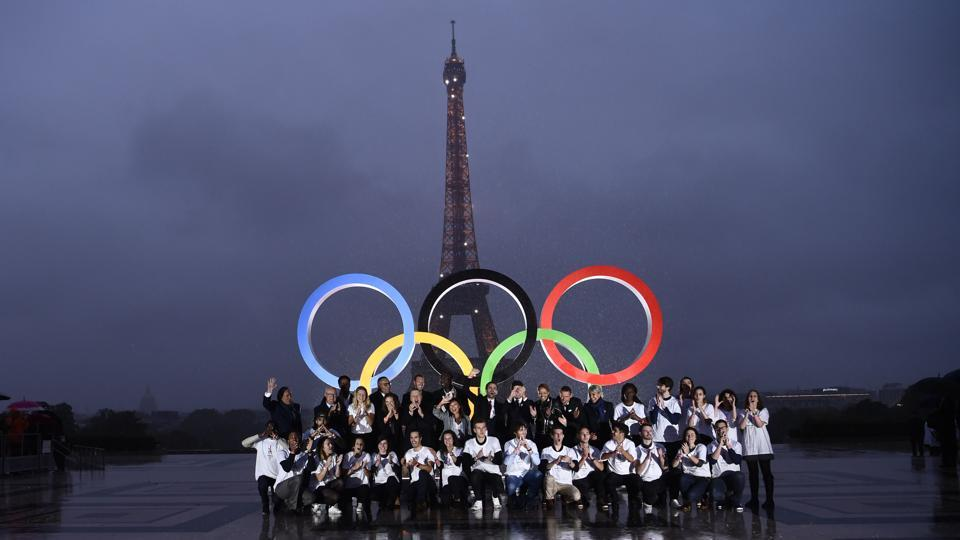 Volunteers pose in front of the Olympics Rings on the Trocadero Esplanade near the Eiffel Tower in Paris, on September 13, 2017.  (AFP)