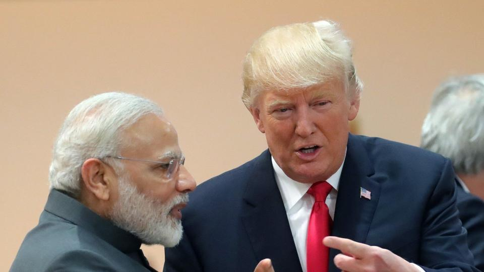 US President Donald Trump (R) talks with Narendra Modi as they attend a working session during the G20 summit in Hamburg, northern Germany, on July 8, 2017.