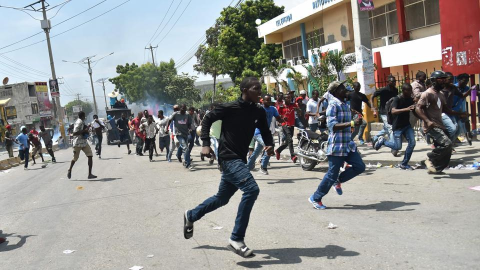 Demonstrators run for cover as Haitian police fire tear gas to disperse an anti-government protest in the centre of the Haitian capital Port-au-Prince. 'To renew your driving license, you must now show a receipt confirming you have paid 10,000 gourdes ($158), no matter if you are a poor taxi driver or a street vendor,' claimed Jean Claude Reimbold. The National Identity Office, which produces the cards, denied Monday the free document would cost 1,000 gourdes once the new budget comes into effect. (Hector Retamal / AFP)
