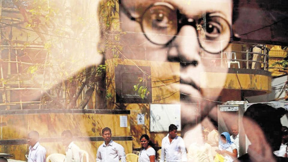 People are reflected on the glass of a framed photograph of Bhimrao Ambedkar, as they visit a memorial dedicated to him, on his birth anniversary in Mumbai on April 14, 2016.
