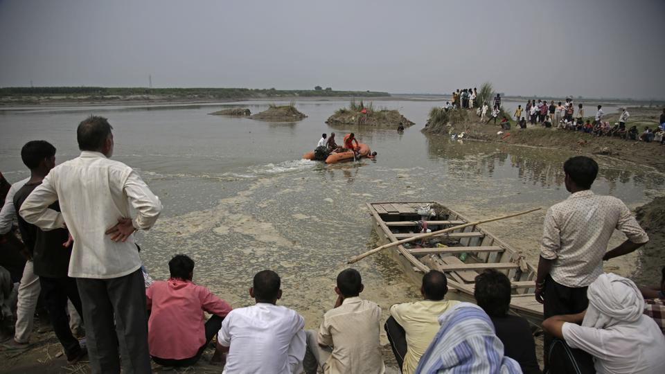 Rescuers search in the Yamuna River as villagers gather after a country boat capsized near Baghpat town in Uttar Pradesh.