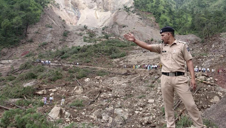 A policeman gestures at the site of a landslide on August 14 in Himachal Pradesh.