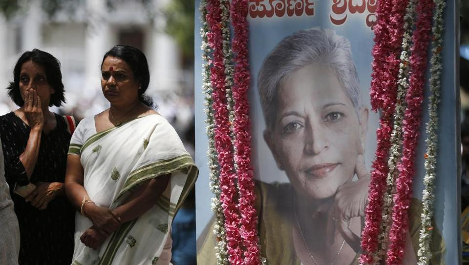 Mourners stand next to a portrait of slain journalist Gauri Lankesh during the public viewing of her body in Bengaluru on September 6, 2017.