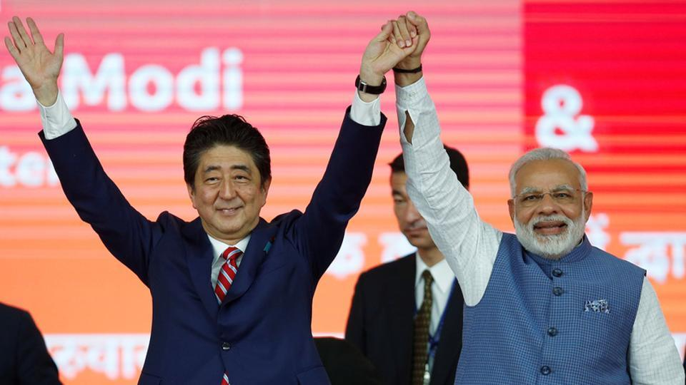Japanese Prime Minister Shinzo Abe (L) and his Indian counterpart Narendra Modi raise hands after the groundbreaking ceremony for a high-speed rail project in Ahmedabad.
