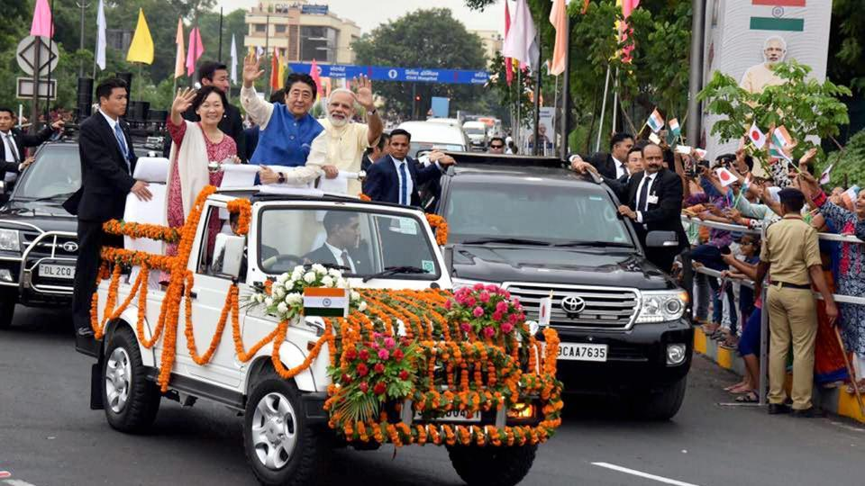 Prime Minister Narendra Modi, Japanese Prime Minister Shinzo Abe and his wife Akie Abe wave from an open vehicle during their roadshow in Ahmedabad on Wednesday. Abe is on a two-day visit to India.