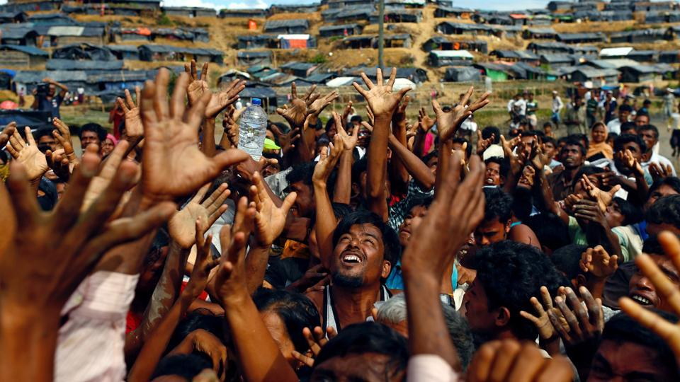 Rohingya refugees stretch their hands to receive aid distributed by local organisations at Balukhali makeshift refugee camp in Cox's Bazar, Bangladesh, on September 14, 2017.