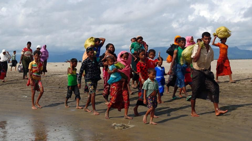 Rohingya refugees walk on the shore after crossing the Bangladesh-Myanmar border by boat through the Bay of Bengal in Shah Porir Dwip, Bangladesh, on September 11, 2017.