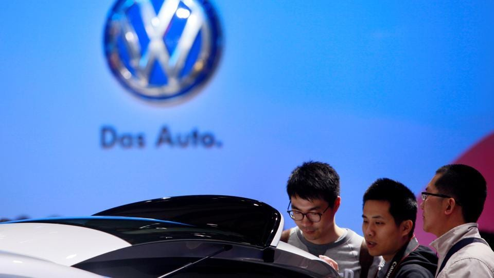 Guests look at a Volkswagen car during the media day at 15th Shanghai International Automobile Industry Exhibition in Shanghai April 20, 2013.