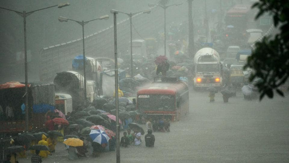 People wade along a flooded street during heavy rain showers in Mumbai on August 29, 2017. Heavy rain brought India's financial capital Mumbai to a virtual standstill on August 29, flooding streets, causing transport chaos and prompting warnings to stay indoors. Dozens of flights and local train services were cancelled as rains lashed the coastal city of nearly 20 million people. / AFP PHOTO / PUNIT PARANJPE