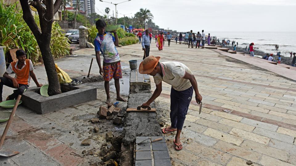 Workers repair promenade at Bandstand in Mumbai on Wednesday.