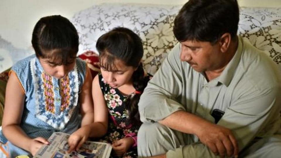 Laeeq Shah, the father of Noreen -- who was killed by a stray bullet during celebratory gunfire when Pakistan won the ICC Champions trophy against its arch rival India -- with his surviving daughters.