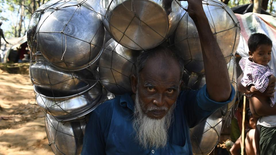 An old Rohingya Muslim refugee carries cooking pots in Bangladesh's Balukhali refugee camp on September 15, 2017.