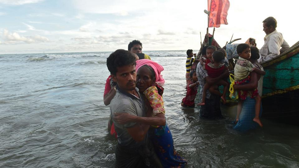 Rohingya refugees disembark from a boat after crossing the border from Myanmar, on the Bangladeshi shores of the Naf river in Teknaf on Thursday.