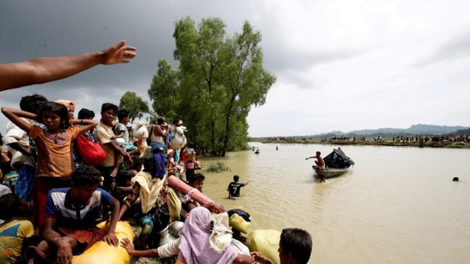 Rohingya refugees wait for a boat to cross a canal after crossing the border through the Naf river in Teknaf, Bangladesh.