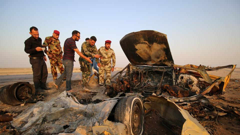 Iraqi security forces inspect the site of a bomb attack at a police checkpoint on a highway near the southern Iraqi city of Nassiriya, Iraq, September 14, 2017.