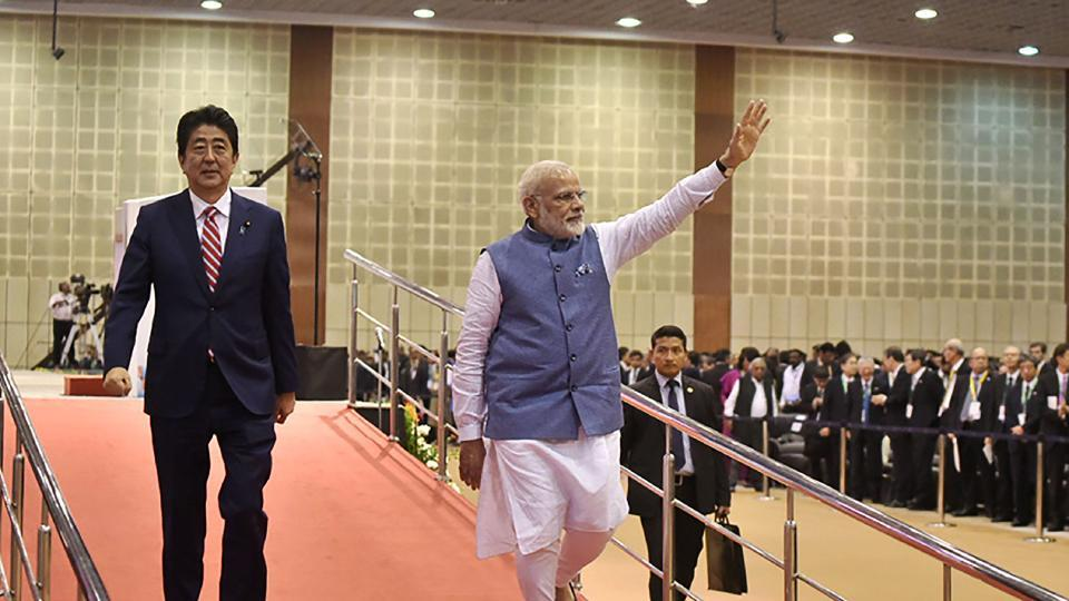 This handout photograph released by India's Press Information Bureau (PIB) on September 14, 2017 shows Indian Prime Minister Narendra Modi (R) and Japanese Prime Minister Shinzo Abe (L) arriving for the India-Japan Business Summit at the Mahatma Mandir convention center in Gandhinagar in Gujarat state.