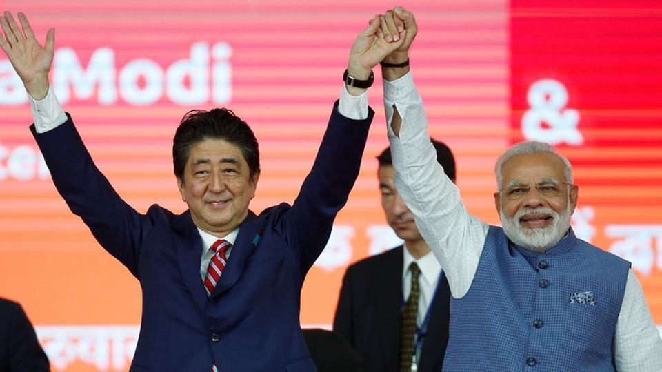 Japanese Prime Minister Shinzo Abe (L) and his Indian counterpart Narendra Modi raise hands after the groundbreaking ceremony for a high-speed rail project in Ahmedabad, September 14.