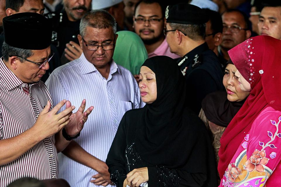 Chief Minister of Terengganu Ahmad Razif talks with family members of the victims inside the forensics wing of the Hospital Kuala Lumpur, where the body of Darul Quran Ittifaqiyah religious school victims are being kept in Kuala Lumpur on September 15, 2017. Malaysian authorities said they had not ruled out foul play in a fire that killed 23 children and teachers in a religious school, as calls mounted for better safety regulations in Islamic study centres. / AFP PHOTO / SADIQ ASYRAF