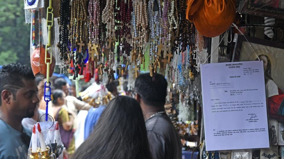 Stall owners display permits at their booths outside Mount Mary church in Bandra on Thursday.