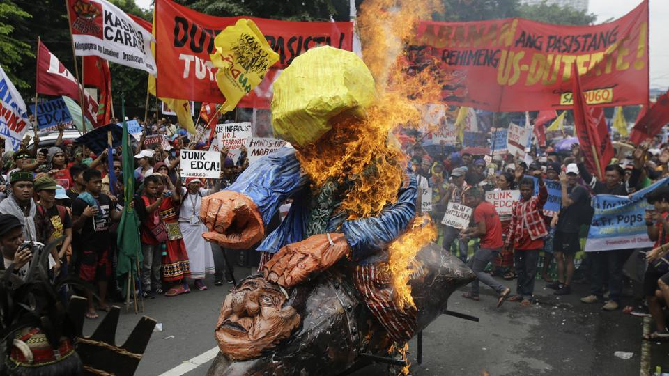 Protesters burn an effigy of U.S. President Donald Trump riding on a missile with an image of Philippine President Rodrigo Duterte as they tried to march towards the U.S. Embassy in Manila, Philippines, Friday, Sept. 15, 2017.