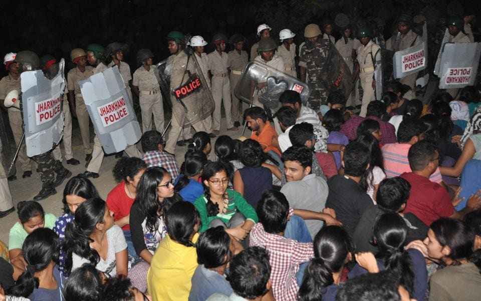 Policemen watch as students of the National University of Study and Research in Law stage a dharna against the alleged misappropriation of funds in front of university gate at Kanke in Ranchi.