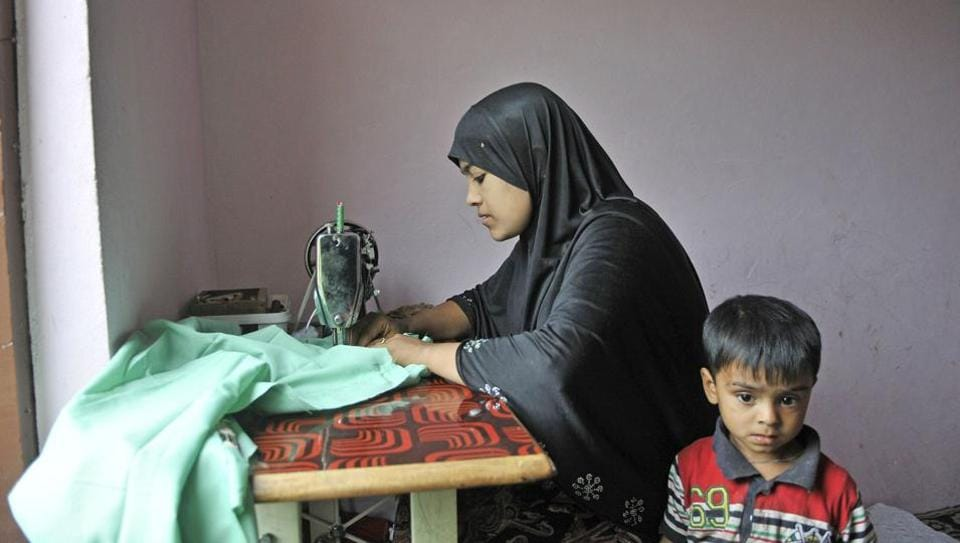 Yasmeen, a Rohingya refugee from Myanmar, stitches clothes inside a house on the outskirts of Srinagar.