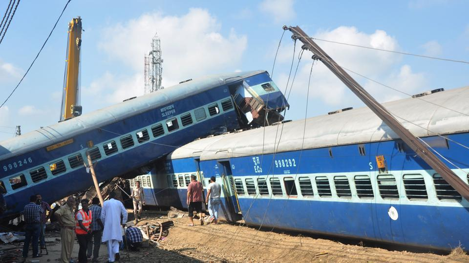 Policemen and emergency crew stand next to the wrecage of a train carriage after an express train derailed on the evening of August 19 near the town of Khatauli in the state of Uttar Pradesh, on August 20, 2017.