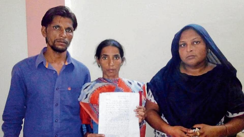 Tikka Masih's wife Sunita and others showing the written complaint she has made to police.