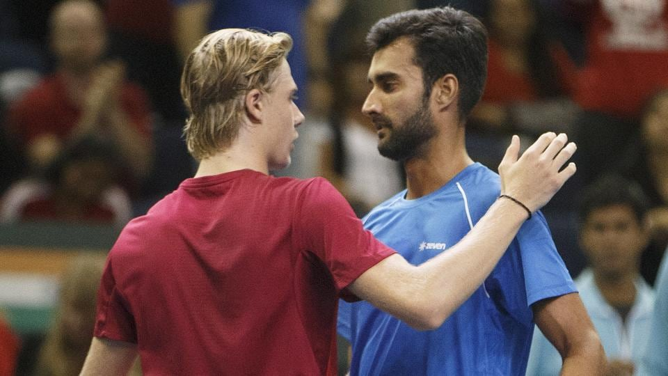 Denis Shapovalov is congratulated by Yuki Bhambri after his 7-6(2), 6-4, 6-7(8), 4-6, 6-1 win.  (AP)