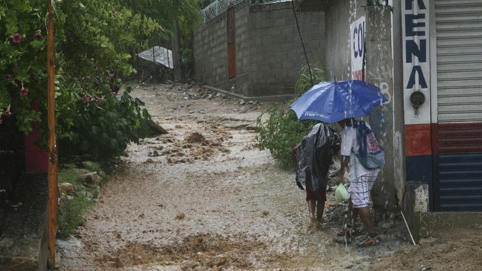People walk under a downpour on a flooded street in Guerrero state, Mexico, on September 14 after hurricane Max hit the southern Pacific coast. Another hurricane, Norma, is expected to strengthen during the next couple of days.